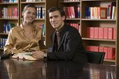 picture of shelving unit  - Portrait of a smiling young man and woman sitting at desk in the library - JPG