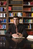 image of shelving unit  - Thoughtful young man in formals with book at desk in library - JPG