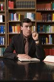 picture of shelving unit  - Thoughtful young man in formals chewing pen at desk in library - JPG