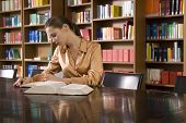stock photo of shelving unit  - Beautiful young woman studying at desk in library - JPG