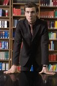 pic of shelving unit  - Serious young man in suit leaning on desk in the library - JPG