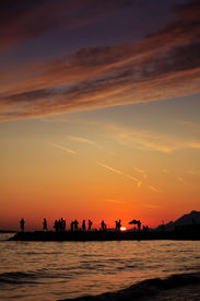 stock photo of beach party  - Silhouettes of people having fun on the dock - JPG