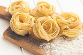 foto of cutting board  - Italian pasta tagliatelle and flour on cutting board - JPG