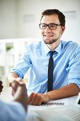 picture of negotiating  - Smiling businessman handshaking with partner after negotiations - JPG