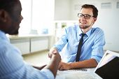stock photo of congrats  - Image of two young businessmen making deal at meeting in office - JPG