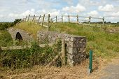 pic of old stone fence  - An old stone bridge overgrown with grass with a rickety wooden fence - JPG