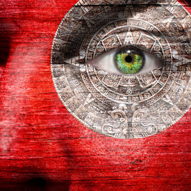 stock photo of superimpose  - Red face with Mayan Calendar superimposed around the eye - JPG