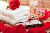 stock photo of swedish sauna  - roses rose petals rose extract bottles bathing salt and a towel - JPG