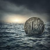 stock photo of stagnation  - Ruble coin sinking in water - JPG