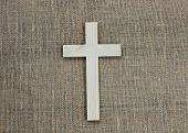 stock photo of lent  - Wooden cross hanging on textured burlap wall - JPG