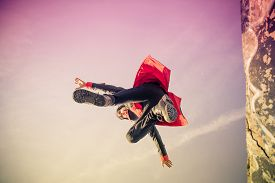 stock photo of parkour  - Parkour athlete jumping over a wall  - JPG