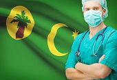 stock photo of coco  - Surgeon with national flag on background  - JPG