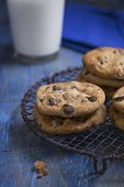 image of racks  - Chocolate Chip Cookies on a rustic cooling rack and blue napkin a glass of milk in the background - JPG