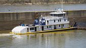 picture of barge  - Blue and White Barge with Yellow Deck Stripe on a River with a Lock Wall - JPG