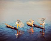 picture of fishermen  - Traditional Burmese fishermen balancing with their fishing net on boats at Inle lake in Myanmar famous for their distinctive one legged rowing style - JPG