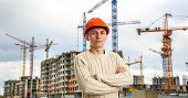 pic of construction crane  - Workman in red helmet on background of buildings under construction and cranes - JPG