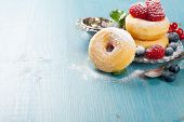 foto of donut  - Morning breakfast with mini donuts and berries on plate under powdered sugar on blue wooden background - JPG