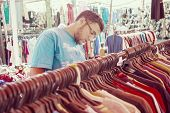 picture of thrift store  - Young man buying in second hand store - JPG