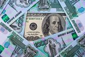 picture of depreciation  - A hundred dollar bill on the background of Russian roubles - JPG
