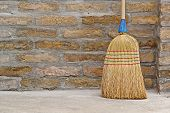 stock photo of broom  - Household Used Broom For Floor Dust Cleaning Leaning on Brick Wall - JPG
