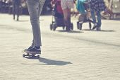 picture of skateboarding  - Young Male Skateboarder Riding Skateboard at City Street Pavement Selective focus Cross Process Toned Image - JPG