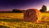 foto of haystack  - Haystack in the field and the motion of the stars in the sky - JPG