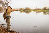 stock photo of fishermen  - Young fisherman fishing on the river bank - JPG