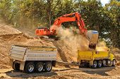 stock photo of dump_truck  - Large track hoe excavator filling a dump truck with rock and soil for fill at a new commercial development road construction project - JPG