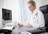 pic of stethoscope  - Serious Adult Woman Doctor with Stethoscope on her Shoulders Writing Some Medical Findings on a Paper at her Worktable - JPG