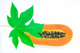 pic of papaya fruit  - Haft cut papaya fruit and papaya leaf isolated over white background Focus on papaya fruit - JPG