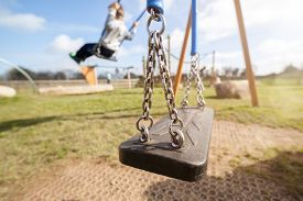 stock photo of swing  - Empty playground swing with children playing in the background concept for child protection - JPG