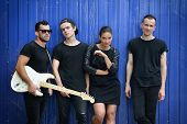 Постер, плакат: Music band outdoor portrait Musicians and woman soloist posing outside against grunge blue fence i