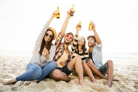 picture of cold drink  - Friends having fun together at the beach and drinking a cold beer - JPG