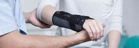 stock photo of stability  - Woman with dislocated wrist in stabilizer is consulting doctor - JPG