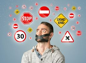 image of traffic signal  - Young man with taped mouth and traffic signals around his head   - JPG