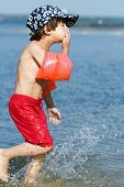 picture of floaties  - five years old boy running and splashing water in a lake with floaty security - JPG