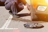 Man Picks Up Car Jack To Change Tire. Car Tires And Wheels With Wheels. Car Service. Change A Flat C poster