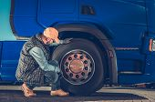 Caucasian Driver Checking Semi Truck Wheels Looking For Potential Issues. Transportation Industry Sa poster