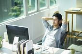 Young Asian Business Man Entrepreneur Contemplating In Office, Hands Behind Head Frowning. poster