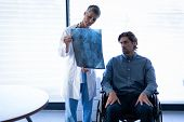 Front view of mature Caucasian female doctor showing x-ray report to Caucasian patient in wheelchair poster