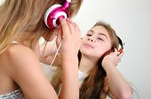 picture of gril  - two young grils with headphones listening to music - JPG