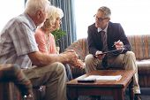 Front view of matured Caucasian male physician interacting with senior Caucasian couple at retiremen poster