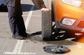 Driver Is Screwing And Unscrewing Changing Car Wheel By Wrench. Change A Flat Car Tire On Road. Auto poster