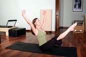 foto of hamstring  - Horizontal image of a pretty young professional Pilates instructor doing Pilates floor exercises - JPG