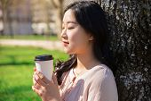 Tranquil Peaceful Girl Enjoying Takeaway Coffee In City Park. Closeup Of Young Asian Woman Leaning B poster