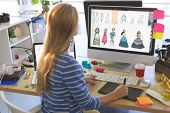 Rear view of young Caucasian blonde female fashion designer using graphic tablet while working at de poster