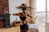Active Woman With Nice Little Braids Stretching Her Back At Home poster