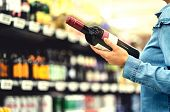 Alcohol Shelf In Liquor Store Or Supermarket. Woman Buying A Bottle Of Red Wine And Looking At Alcoh poster