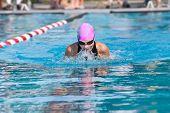 stock photo of swim meet  - Girl swimming breaststroke in a championship meet outside - JPG