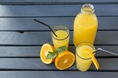 2 Cups Orange Juice With Mint And Straws, A Bottle Of Orange Juice, A Piece Of Orange ,half A Fresh  poster